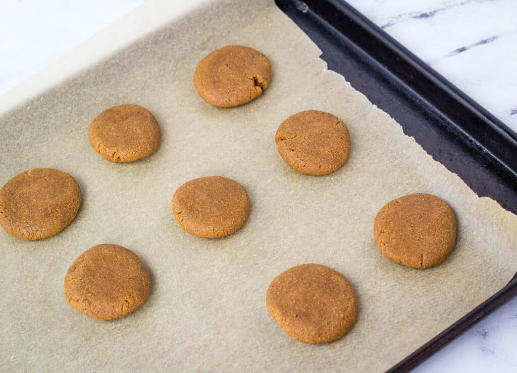 flattened cookie dough balls on baking sheet