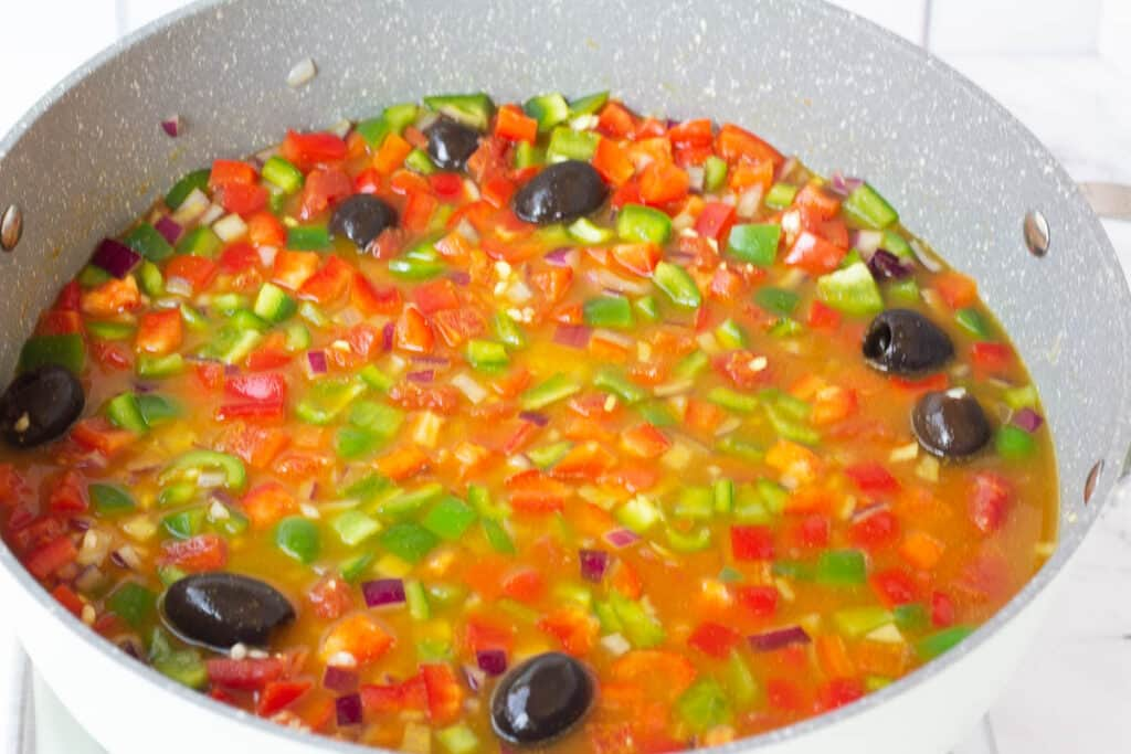 rice, vegetables, and olives covered with stock