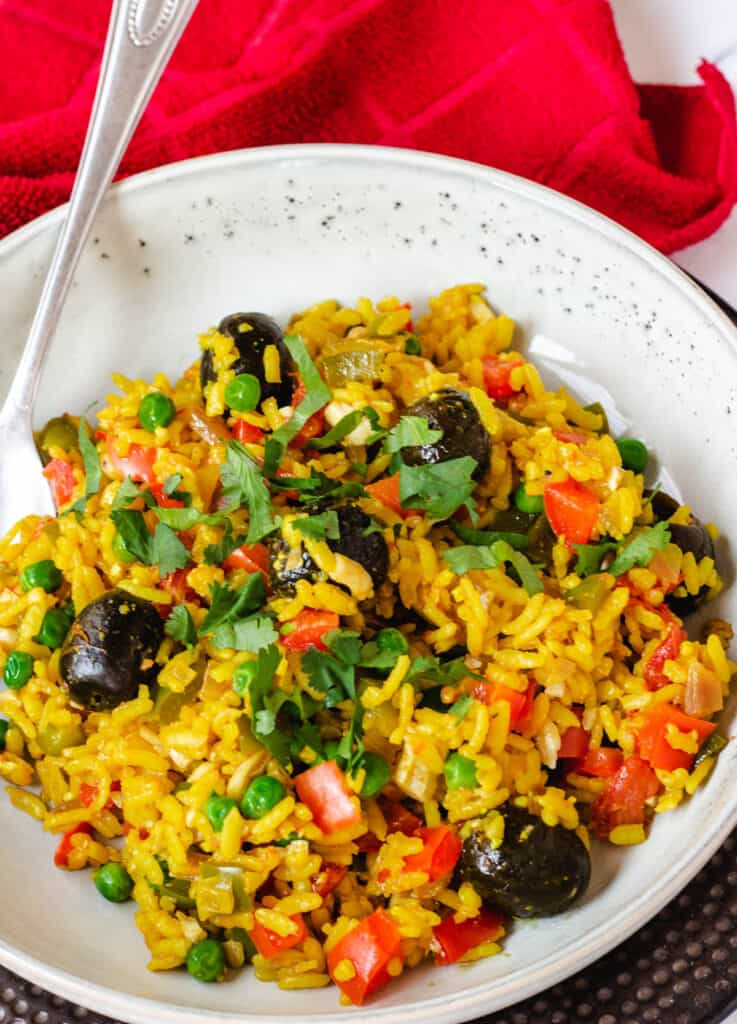 vegetable paella topped with olives and cilantro