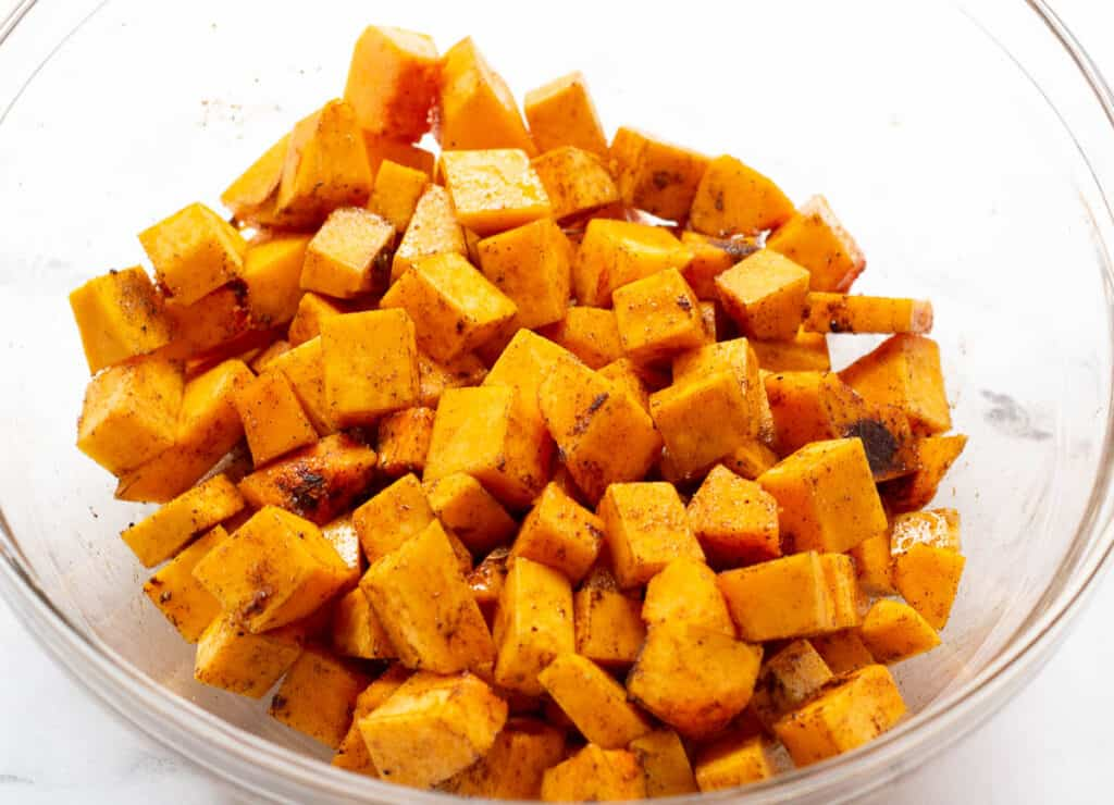 butternut squash in glass bowl tossed with spices