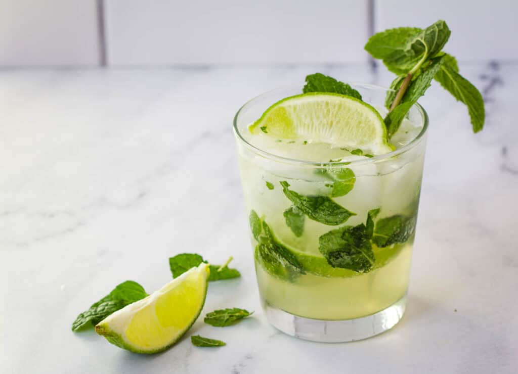 mojito mocktail in rocks glass next to a wedge of lime and mint leaves