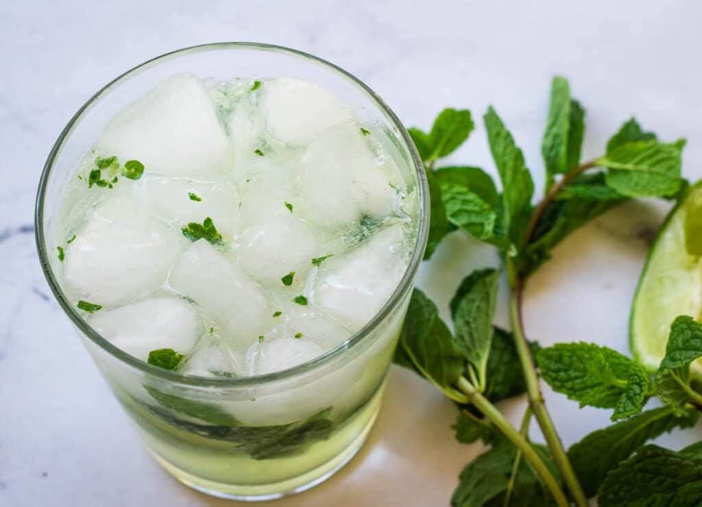 rocks glass filled with ice, club soda, mint, and lime