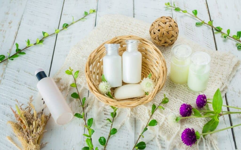 shampoo and conditioner bottles in basket on natural background