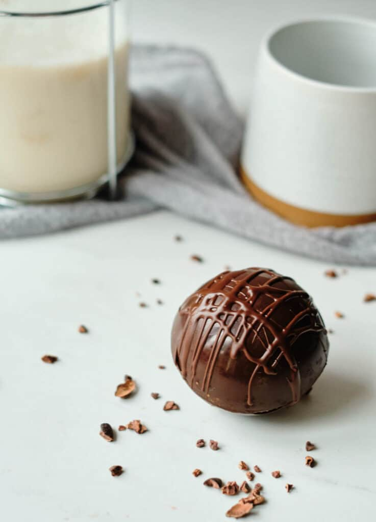 chocolate ball drizzled with chocolate with mug and milk in background