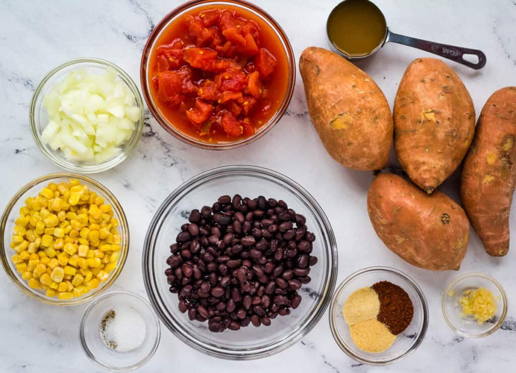vegan loaded sweet potato ingredients: corn, onion, diced tomatoes, black beans, garlic, spices, and sweet potatoes