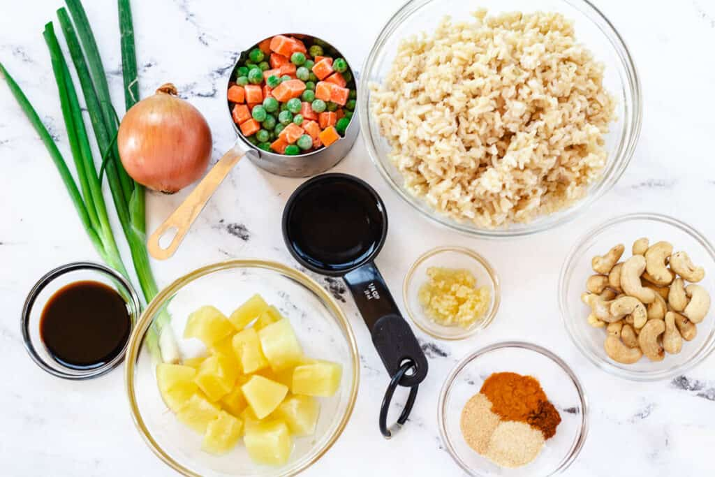 pineapple fried rice ingredients: scallions, peas and carrots, brown rice, pineapple, garlic, spices, cashews, fish sauce, and vegetable stock