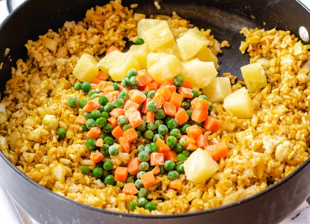 fried rice in pan with pineapple, peas, and carrots