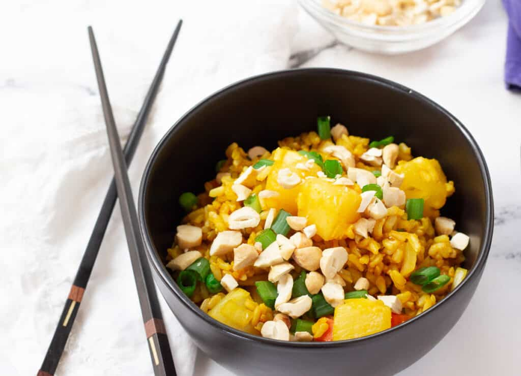 fried rice topped with pineapples scallions, and cashews