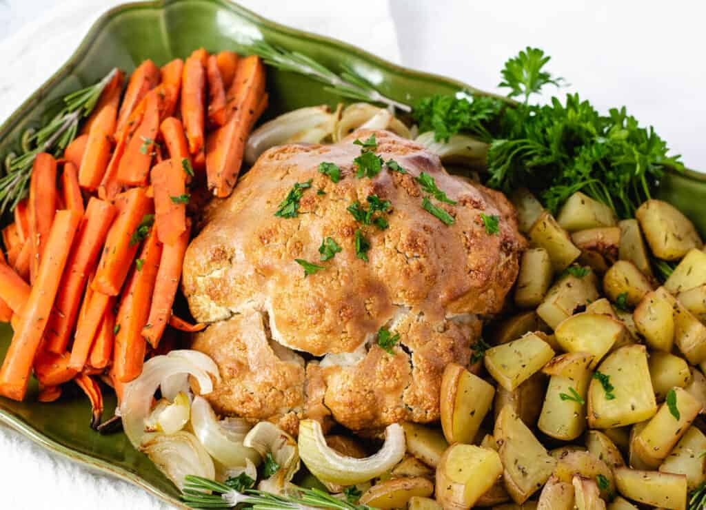 vegan roast dinner on platter. cauliflower, potatoes, carrots, onions, and fresh herbs