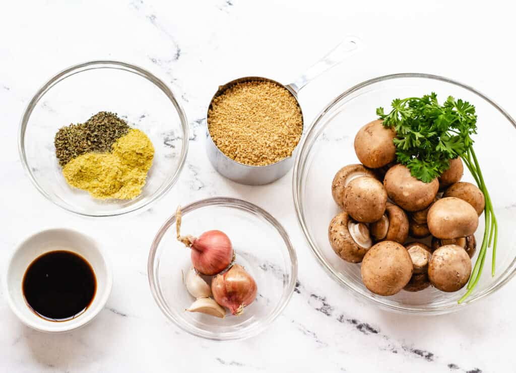 spices and herbs, soy sauce, breadcrumbs, shallots, garlic, mushrooms, and parsley in glass bowl