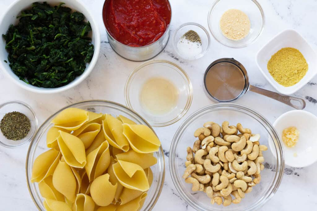 vegan stuffed shell ingredients: jumbo shells, spinach, herbs, tomato sauce, and cashews