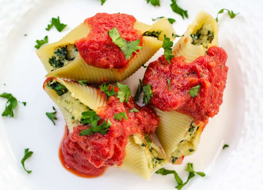 three stuffed shells on white plate topped with marinara sauce and parsley