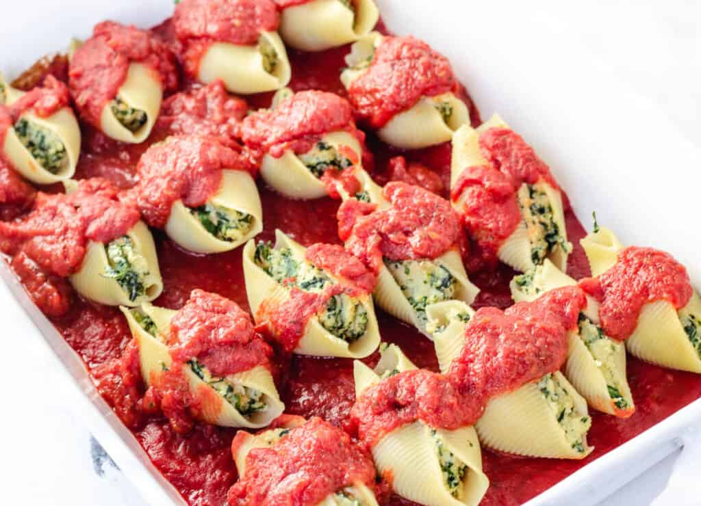 vegan stuffed shells in baking dish topped with tomato sauce