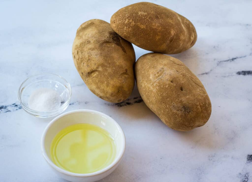 three russet potatoes, salt, and oil on counter top