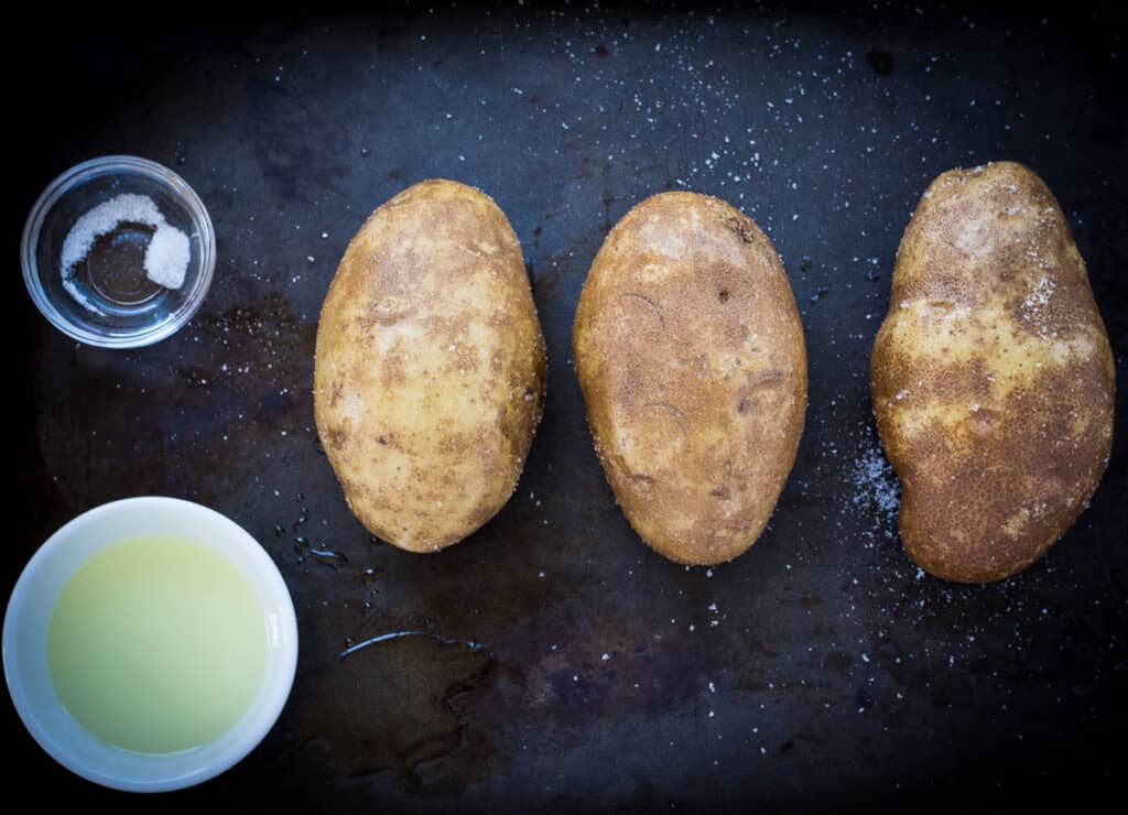 three potatoes on baking sheet covered in oil and salt