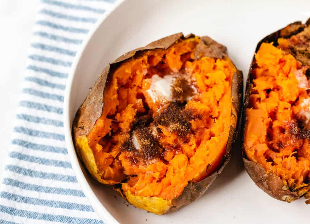 air fryer baked sweet potato in white bowl topped with butter and brown sugar