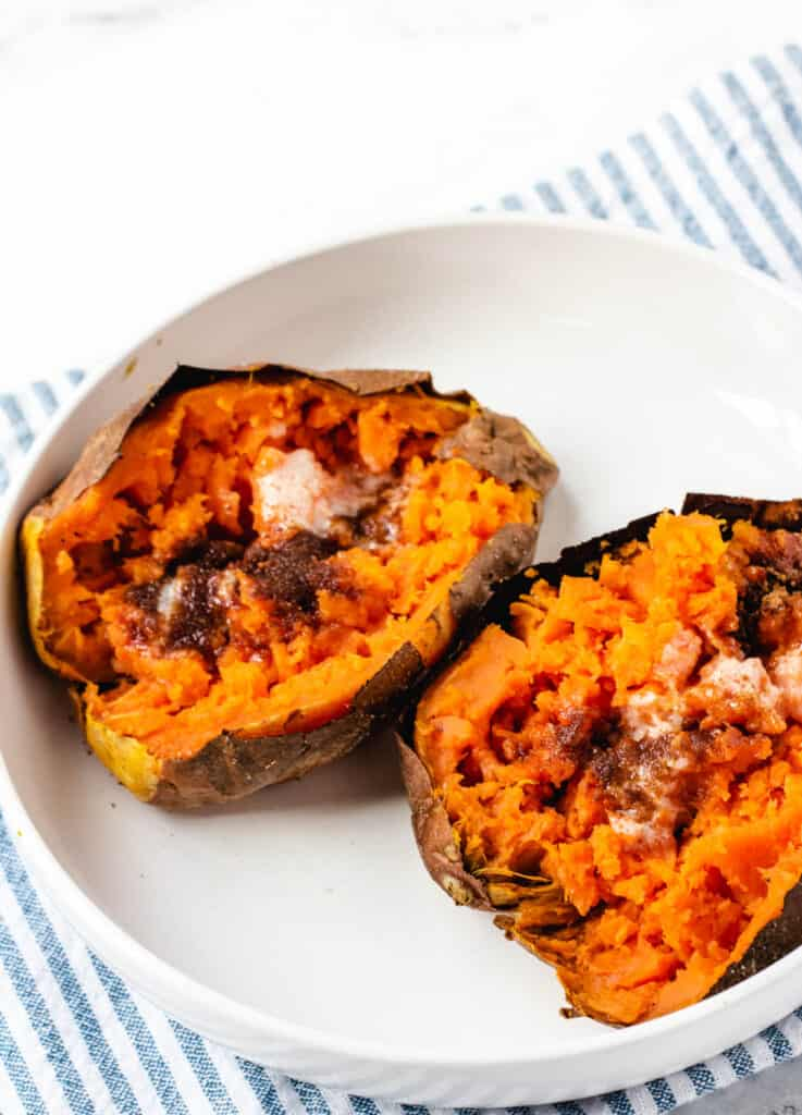 2 air fryer baked sweet potatoes in white bowl topped with butter and brown sugar