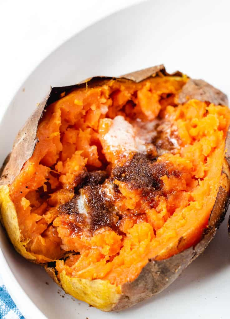 baked sweet potato with butter and brown sugar in white bowl