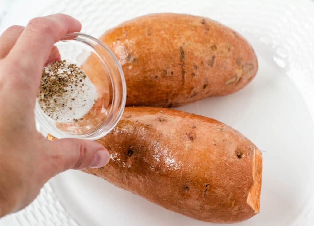 hand sprinkling salt and pepper on sweet potatoes