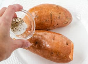 hand sprinkling salt and pepper on sweet potato