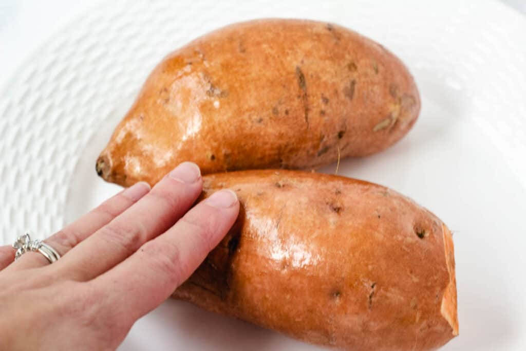 hand rubbing oil on sweet potatoes
