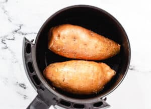 2 sweet potatoes in air fryer basket