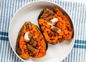 2 baked sweet potatoes topped with butter and brown sugar