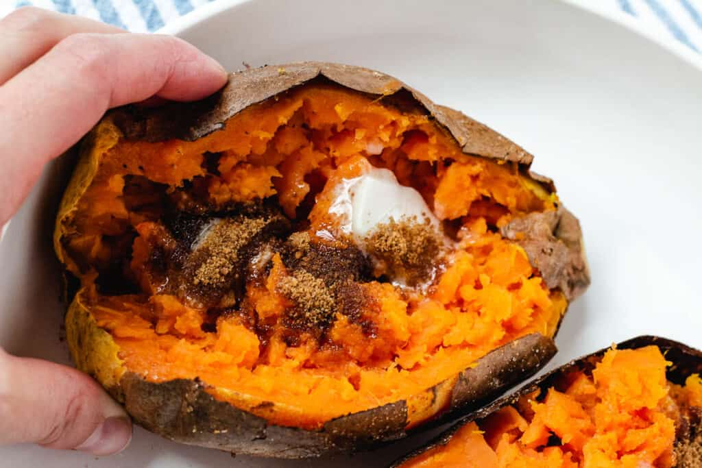 hand holding baked sweet potato topped with butter and brown sugar