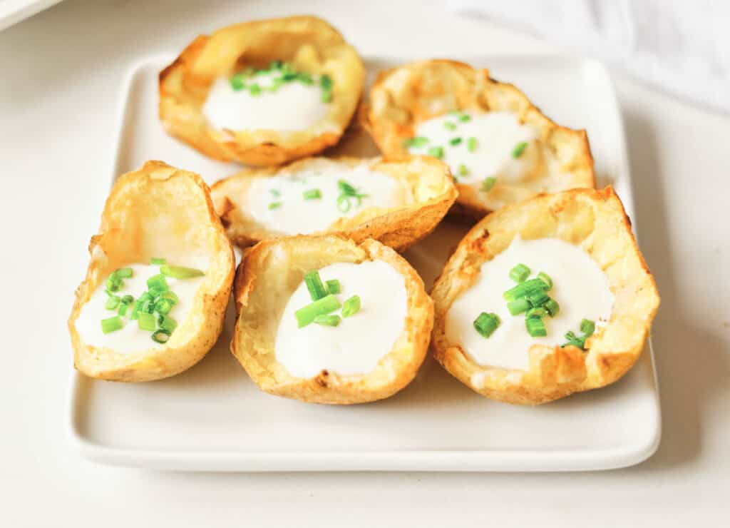 air fryer potato skins on a white square plate filled with cheese, sour cream, and chives