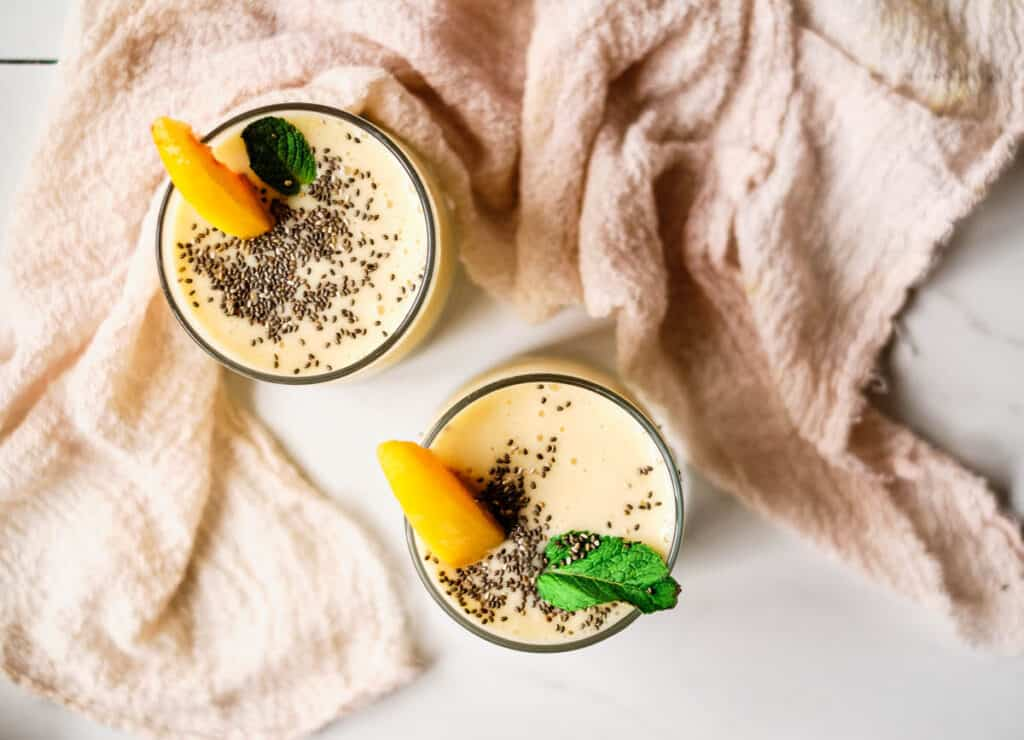 two banana peach smoothies in glasses shot overhead topped with chia seeds, mint, and peach slice