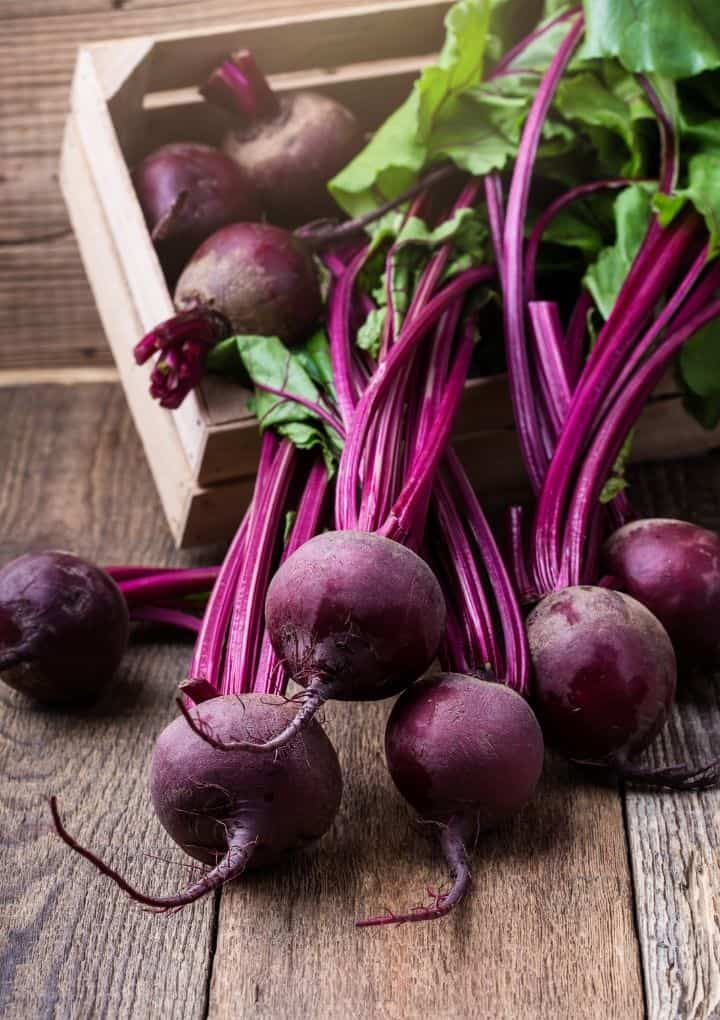 bunch of beetroot bulbs attached to their stems on a wood table and in a wood box