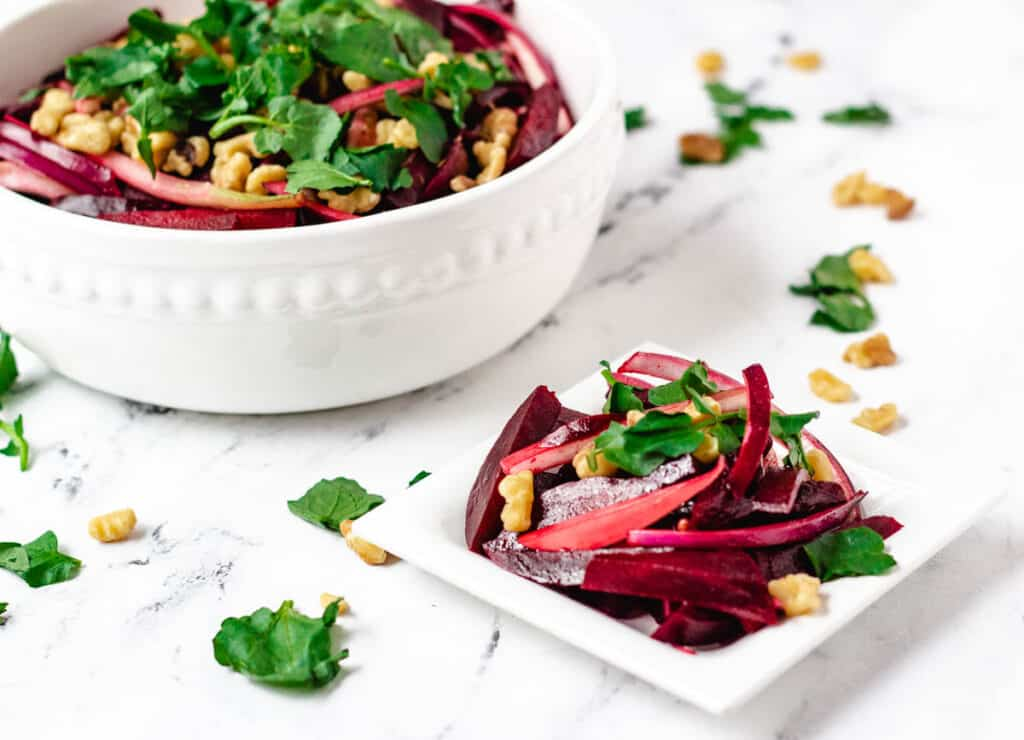 beetroot salad in white serving bowl next to small serving size of salad on white dish