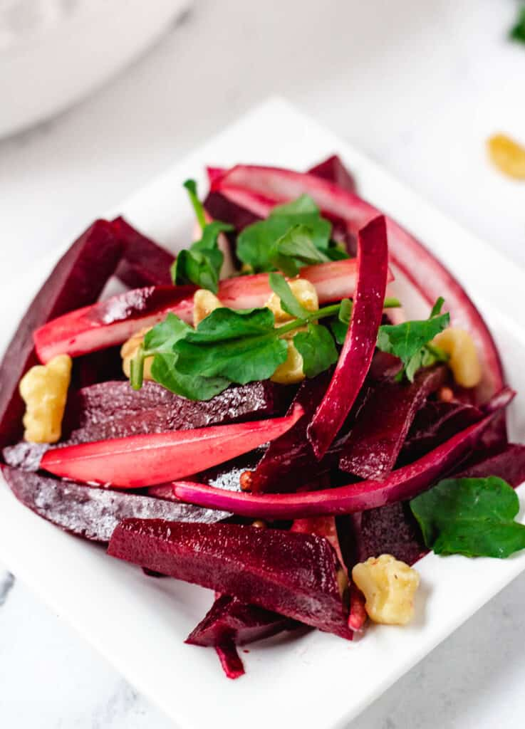 small serving of beet salad on white plate topped with watercress and walnuts