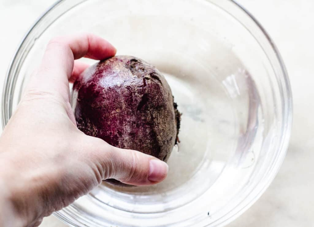 washing beetroot bulb in bowl of cold water