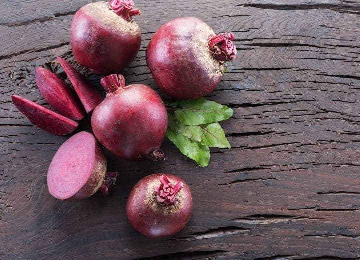 5 raw beetroot bulbs, one sliced, others with partial stem attached on wood table