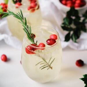 orange moctail garnished with cranberries and rosemary