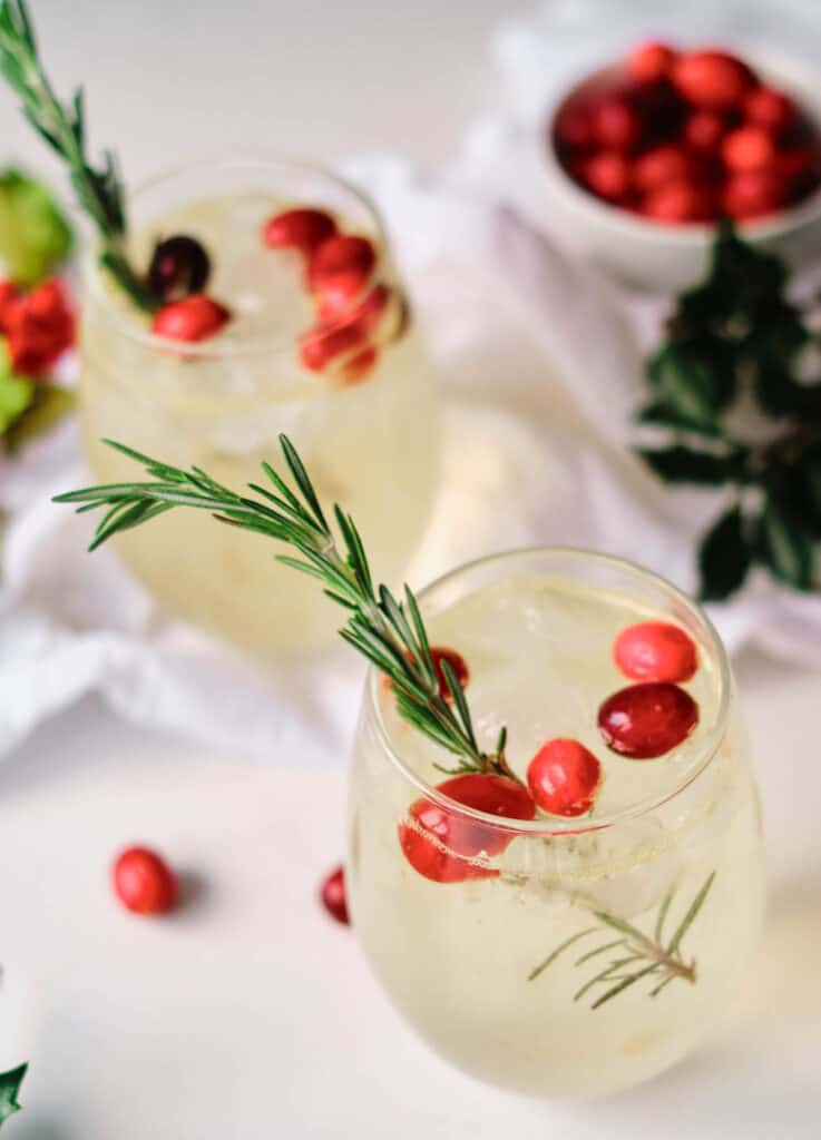 stemless wine glasses filled with flavored water garnished with cranberries and rosemary