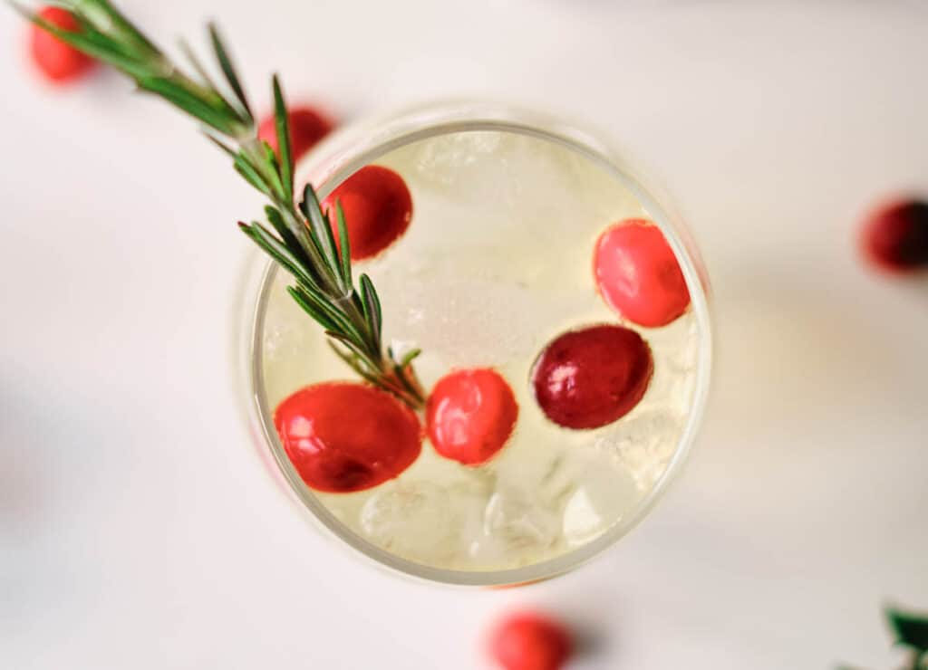 overhead of orange mocktail with cranberries and rosemary