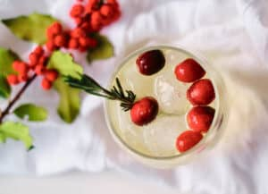 overhead shot of orange moctail topped with cranberries and rosemary