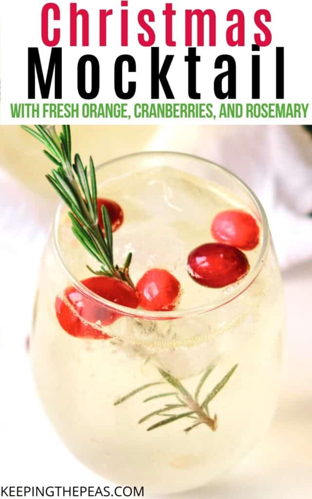 sparkling holiday mocktail with cranberries and a sprig of thype