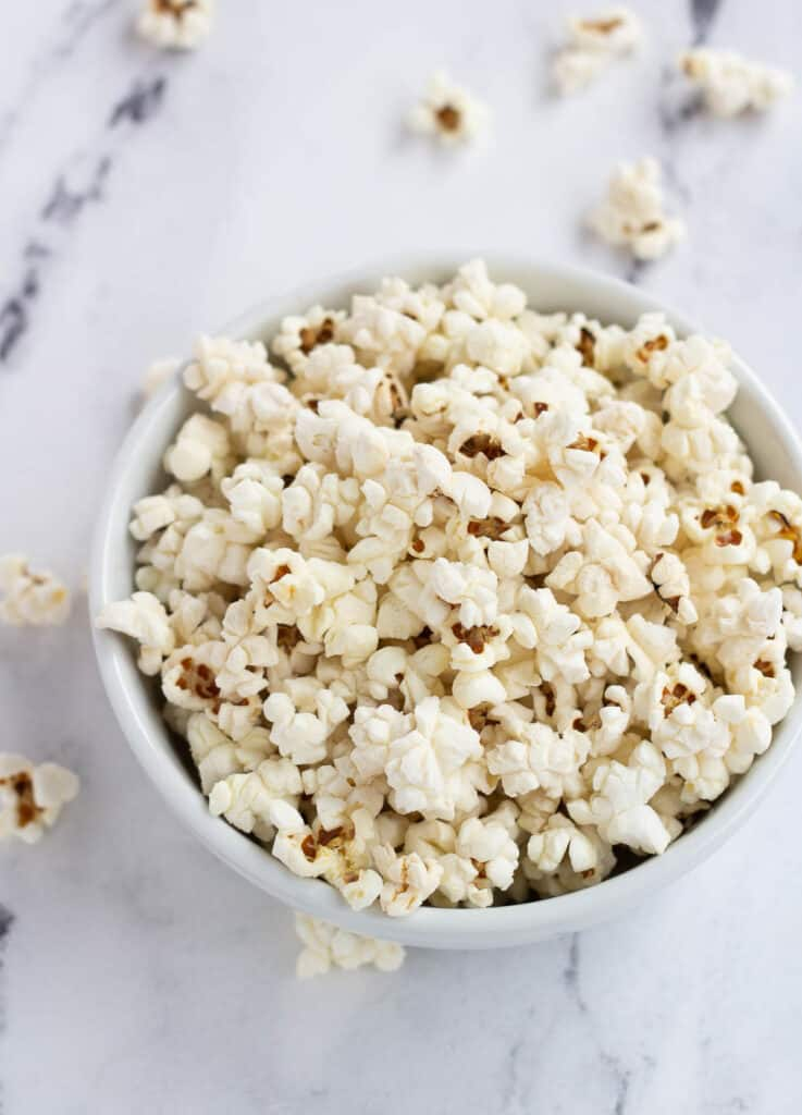 salted vegan popcorn in a white bowl on marble counter
