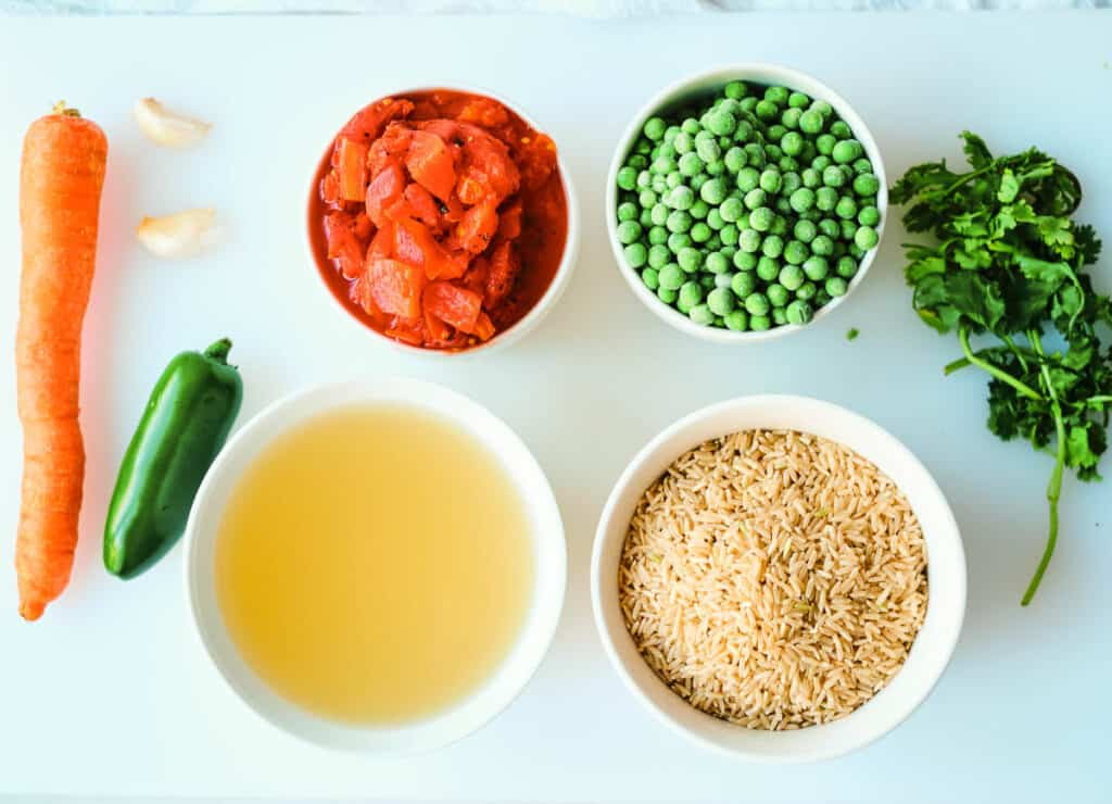 ingredients for arroz rojo on cutting board: 1 carrot, 1 jalapeño pepper, two cloves of garlic, vegetable broth, fire roasted tomatoes, frozen peas, rice, and cilantro