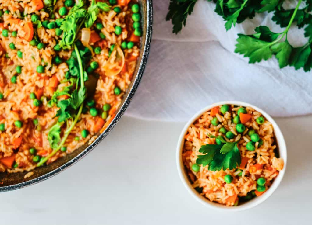arroz rojo in pot and small side in white bowl topped with cilantro