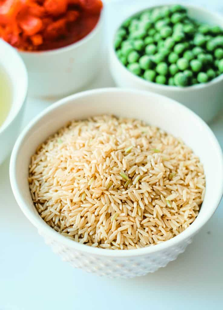 uncooked brown rice in white bowl