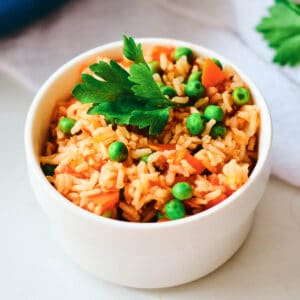 arroz rojo in small white bowl topped with cilantro