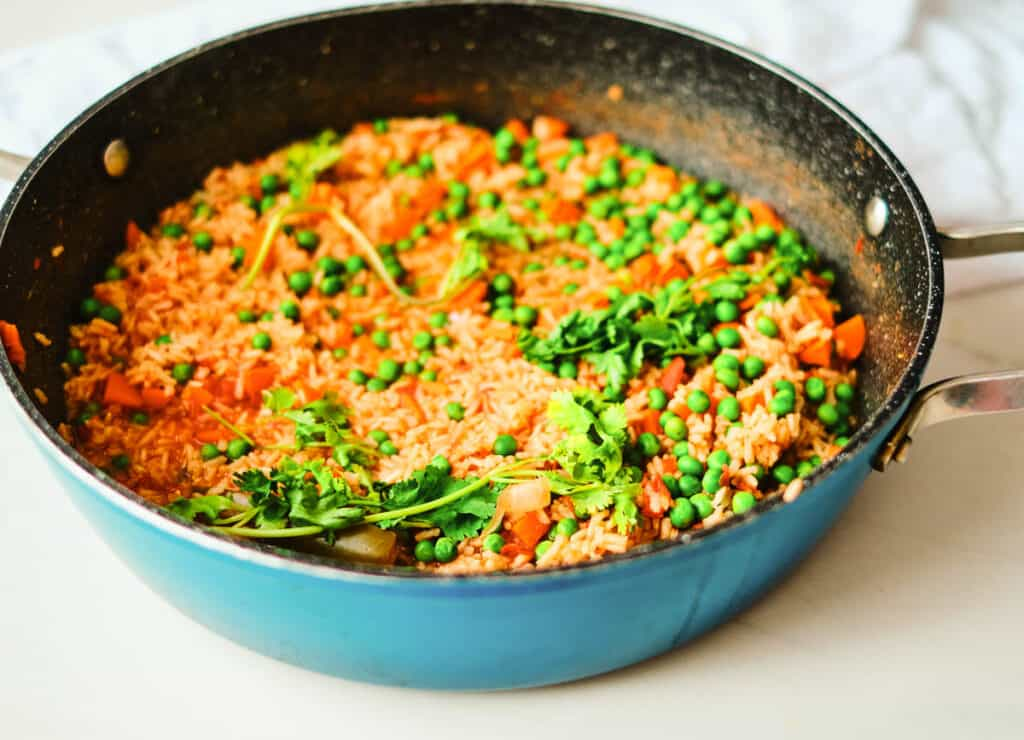 Mexican red rice in blue pot topped with peas and cilantro