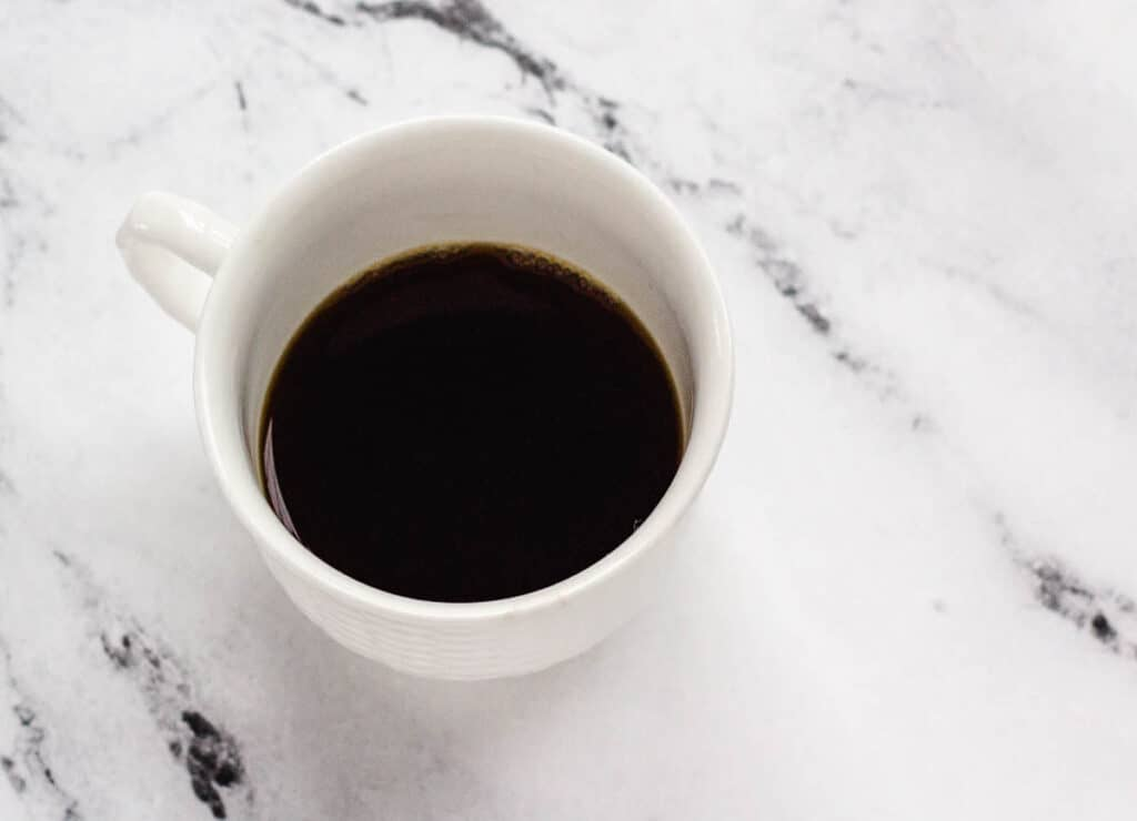small white mug filled half with black coffee