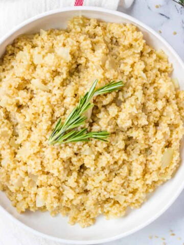 bulgar pilaf in white bowl topped with rosemary sprig