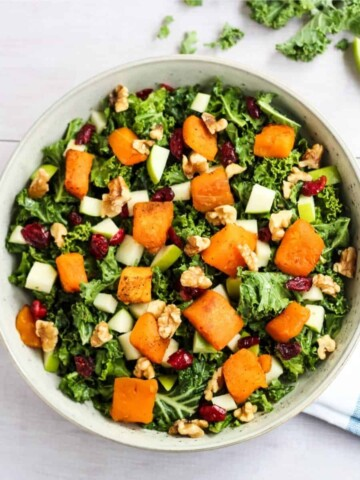 overhead of kale salad topped with roasted butternut squash, cranberries, and nuts. A hearty vegan salad recipe
