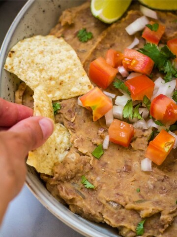 hand scooping vegen refried bean dip with a chip